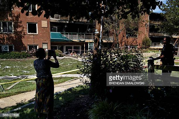 A woman takes a picture while a police officer stands guard after an explosion at Flower Branch Apartments August 11 2016 in Silver Spring Maryland /...