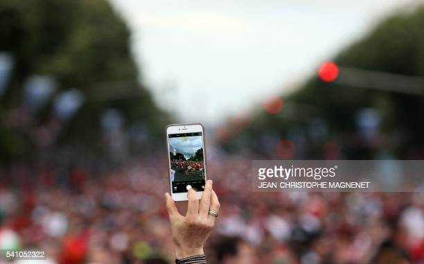 TOPSHOT A woman takes a picture with a mobile phone as Hungary's supporters walk to the Velodrome stadium of Marseille southern France ahead of the...