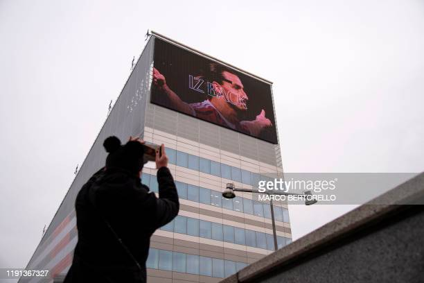 Woman takes a picture with her mobile phone of a large banner of Milan's Swedish forward Zlatan Ibrahimovic on the facade of the club's headquarters...