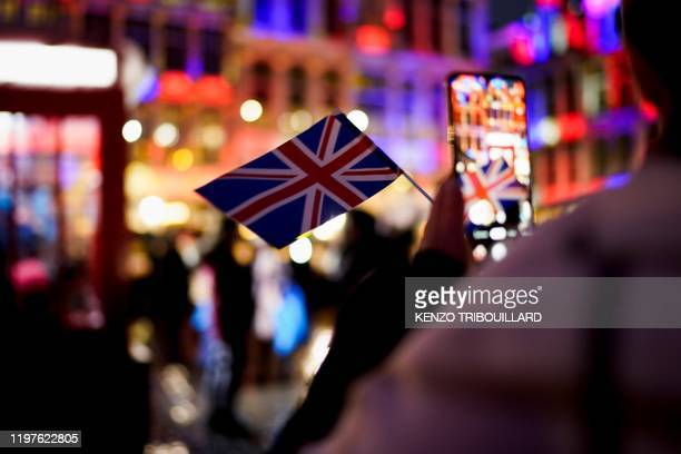 Woman takes a picture with her mobile phone of a Union Jack flag during an event to celebrate the friendship between Belgium and Britain, at the...