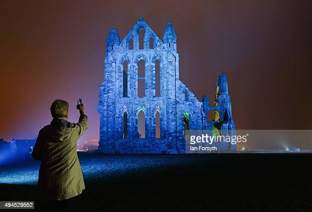 A woman takes a picture with her phone as a spectacular light display illuminates the historic Whitby Abbey on October 27 2015 in Whitby England The...