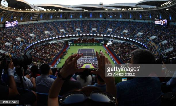 A woman takes a picture with her phone during the men's singles semifinal match between Rafael Nadal of Spain and JoWilfried Tsonga of France at the...