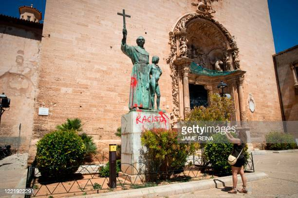 Woman takes a pictured of a statue of the Roman Catholic Spanish priest Junipero Serra in Palma de Mallorca on June 22 after it was daubed with...