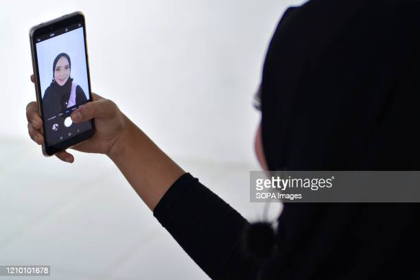Woman takes a selfie after a makeup training. Women in Aceh learn how to apply good makeup during a makeup training. Home cosmetology business in...