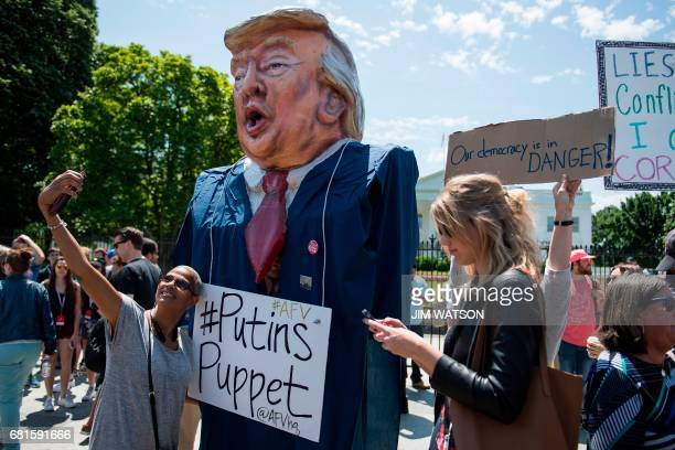 A woman takes a selfie as a protester wears an effigy of Donald Trump in front of the White House during a protest demanding an independent...