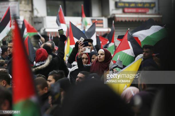 A woman takes a selfie as Palestinian protesters wave national flags during a demonstration against a USbrokered peace proposal in the West Bank city...