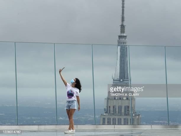 Woman takes a selfie as she looks out over the city from the Edge, the highest outdoor sky deck in the Western Hemisphere on September 2, 2020 as it...
