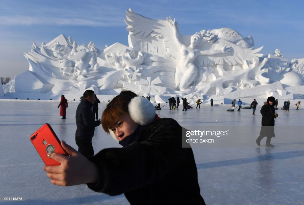 A woman takes a selfie before the opening of the annual Harbin Ice and Snow Sculpture Festival in Harbin in China's northeast Heilongjiang province on January 5, 2018. The festival attracts hundreds of thousands of visitors annually. / AFP PHOTO / Greg Baker