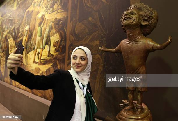 A woman takes a selfie by a statue of Liverpool's Egyptian forward Mohamed Salah displayed at the World Youth Forum in Sharm El Sheikh on November 5...