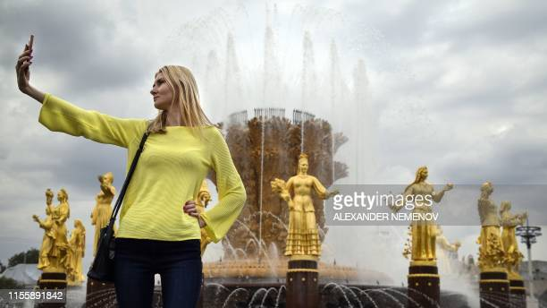 A woman takes a selfie by the Friendship of Nations fountain at VDNKh in Moscow on July 16 2019 The Stalinbuilt permanent general purpose trade show...