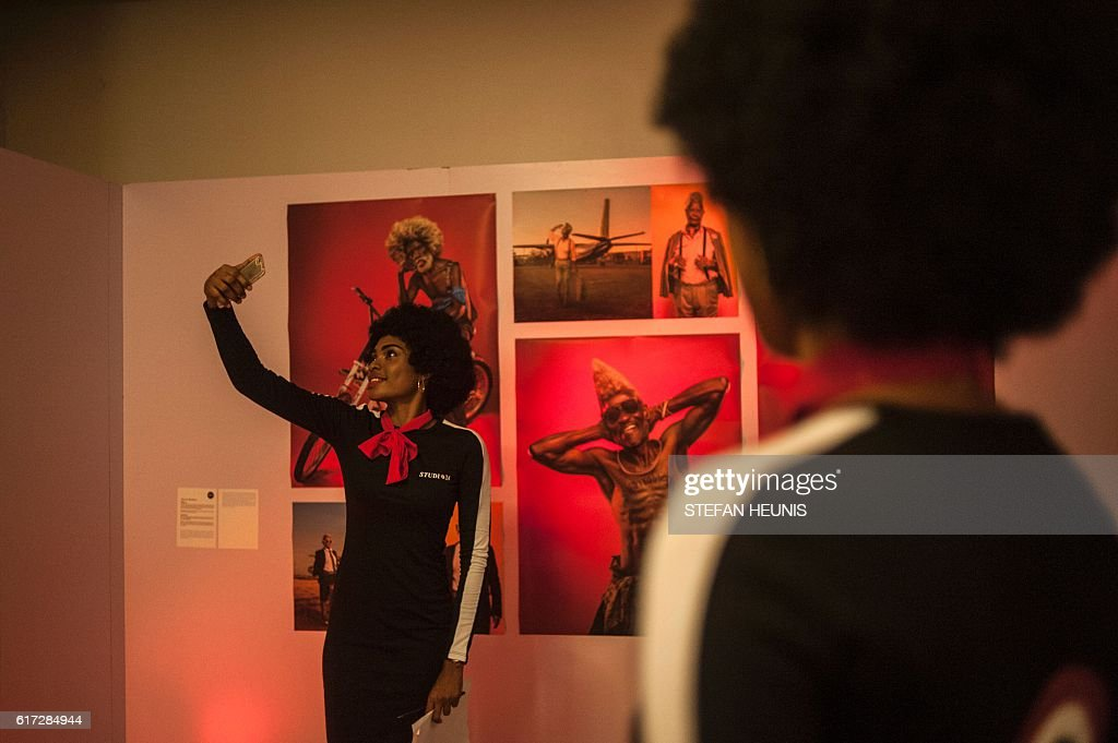 A woman takes a selfie during the opening of the Lagos Photo festival in Lagos on October 22, 2016. Lagos Photo was launched in 2010 and is the first and only international arts festival of photography in Nigeria. / AFP / STEFAN