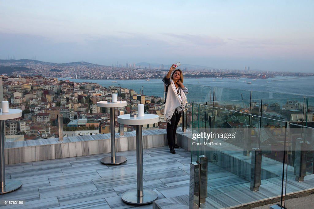 A woman takes a selfie from a rooftop bar at a high end restaurant and popular with tourists and well to do Turks on October 21, 2016 in Istanbul, Turkey. Turkish tourism is struggling from a year of losses, constant instability has driven away western tourists forcing many tourism related businesses to close. Since the failed coup attempt on July 15, 2016 which saw 240 people killed including 173 civilians, Turkish authorities initiated a state of emergency, leading to an unprecedented crackdown on individuals and organizations with links to US-based cleric Fethullah Gulen and his organization blamed for instigating the uprising. The purge, targeting teachers, journalists, soldiers, judges, academics, police, military leaders, schools and universities has so far seen approximately 100,000 people dismissed, 70,000 detained, 32,000 arrested, 130 media outlets closed and some 15 universities shuttered. The failed coup and subsequent purge only appears to have further bolstered the president's popularity and increased nationalism across the country with July 15th having been marked as a new national holiday. Turkish flags, already prominently displaying all over have increased in numbers, as well as posters of those killed fighting the coup plotters appearing in train stations and public squares. The Bosphorus Bridge in Istanbul, which saw heavy fighting during the coup has been renamed the '15th July Martyr's Bridge'. These changes, follow a year of instability in the country with constant terrorist attacks, an economic downturn, plummeting tourism, and a refugee crisis, all contributing to Turkish society undergoing its most dramatic restructuring in decades.