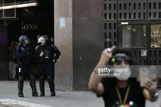 A woman takes a selfie in front of riot police during clashes on the sidelines of a demonstration on April 19 2018 in Paris as part of a multi branch...