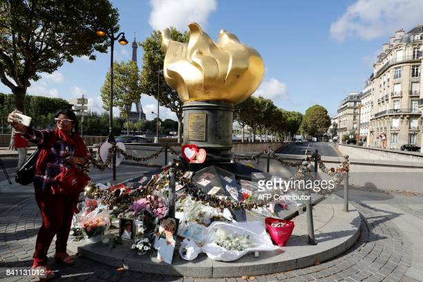 A woman takes a selfie next to the Flame of Liberty monument which became an unofficial memorial for Diana Princess of Wales who died in a car crash...
