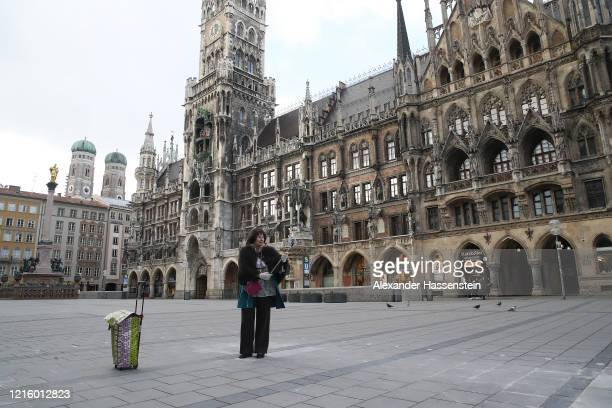 Woman takes a selfie on the empty Marienplatz with the Townhall of Munich during the coronavirus crisis on March 31, 2020 in Munich, Germany. Public...
