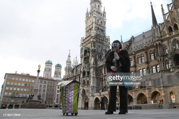 A woman takes a selfie on the empty Marienplatz with the Townhall of Munich during the coronavirus crisis on March 31 2020 in Munich Germany Public...