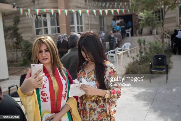 A woman takes a selfie outside a voting station after casting her referendum vote on September 25 2017 in Erbil Iraq Despite strong objection from...
