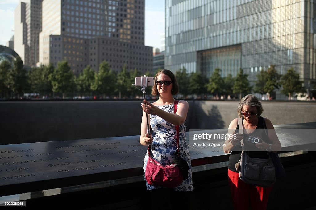 A woman takes a selfie photo as people visit the National 11 September memorial, a day before the 15th anniversary of the 9/11 attacks in Manhattan, New York, USA on September 10, 2016.