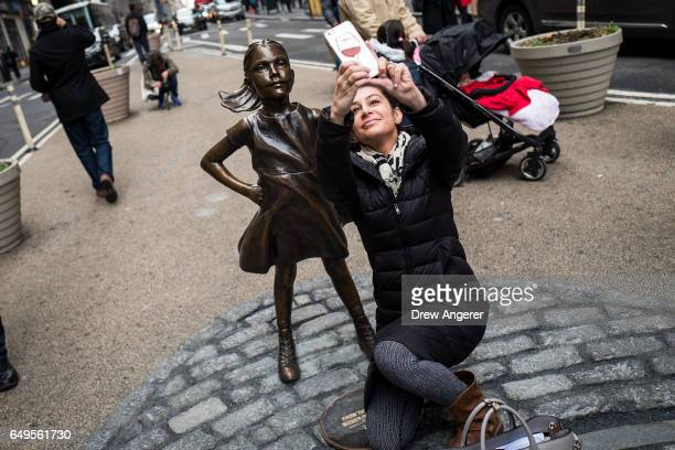 A woman takes a 'selfie' photo with 'The Fearless Girl' statue across from the iconic Wall Street charging bull statue March 8 2017 in New York City...
