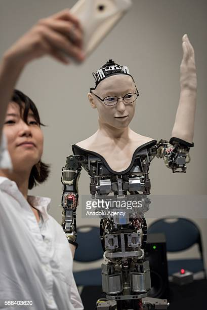 A woman takes a selfie photo with the humanoid robot called Alter designed by scientists in Japan as it is exhibited at the National Museum of...