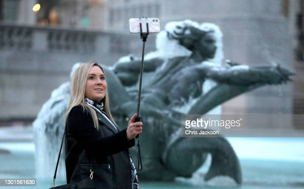 Woman takes a selfie photograph on a smartphone in front of the frozen fountains of Trafalgar Square on February 11, 2021 in London, England. Heavy...