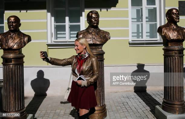 TOPSHOT A woman takes a selfie picture in front of busts of Soviet Leaders Nikita Khrushchev Joseph Stalin and Vladimir Lenin during a ceremony...