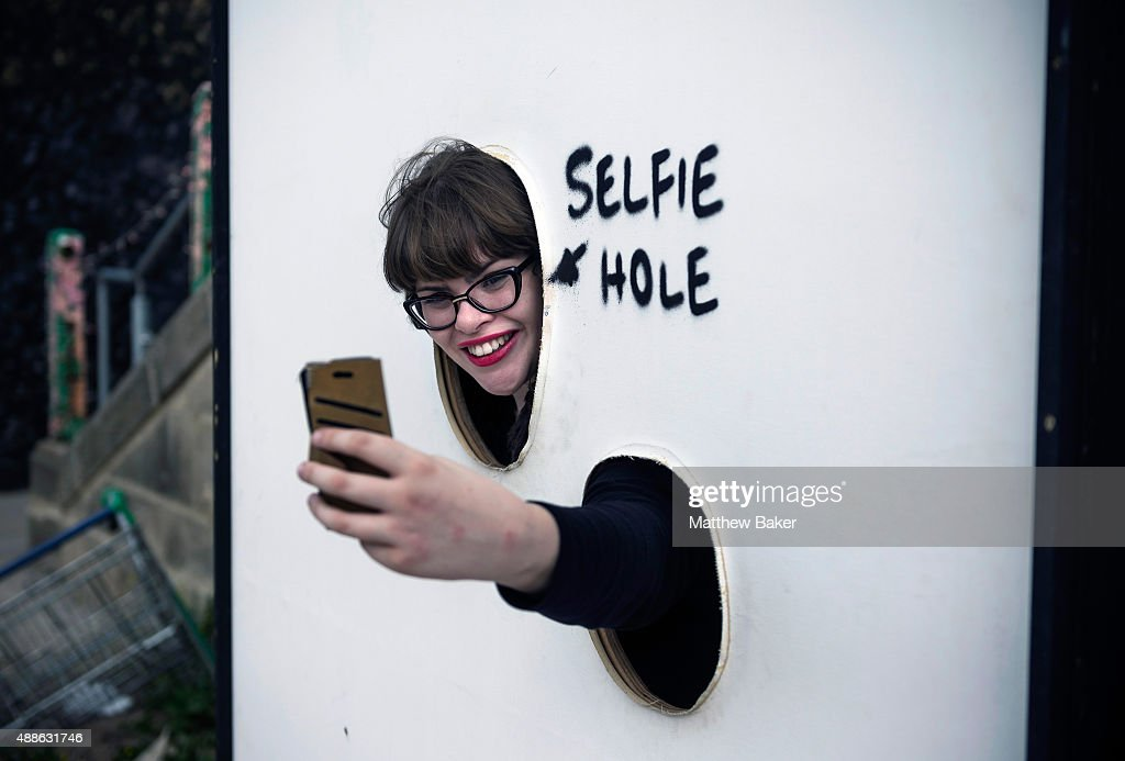 A woman takes a selfie through the 'Selfie Hole' at Banksy's Dismaland on September 10, 2015 in Weston-Super-Mare, England.