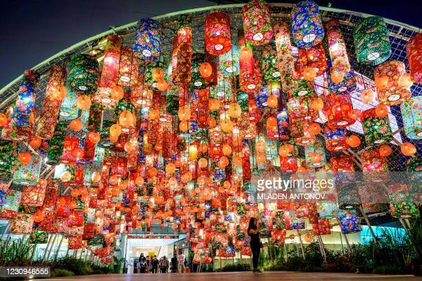 Woman takes a selfie under festive decorations for the upcoming Lunar New Year outside a shopping mall in Bangkok on February 3, 2021.