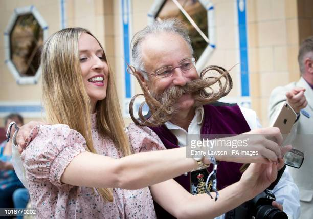 A woman takes a selfie with a competitor of the fourth British Beard and Moustache Championships at the Empress Ballroom Winter Gardens Blackpool