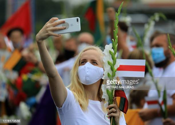 A woman takes a selfie with her phone holding a Belarussian opposition flag as people form a human chain from Vilnius to Medininkai along the border...