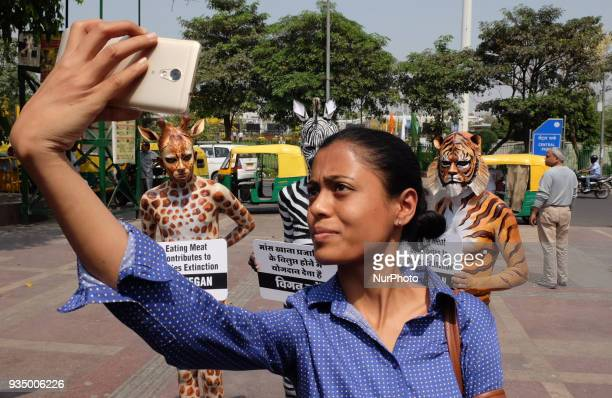 A woman takes a selfie with People for the Ethical Treatment of Animals members bodypainted as a tiger zebra and giraffe standing with signs...