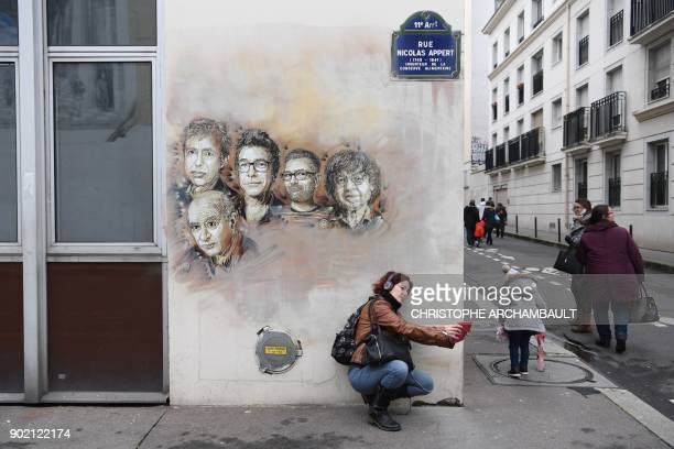 A woman takes a selfie with portraits of late French satirical weekly Charlie Hebdo's deputy chief editor Bernard Maris French cartoonists Georges...