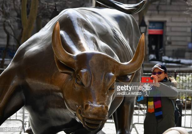 Woman takes a selfie with the 'Charging Bull' statue on February 17, 2021 in New York City.