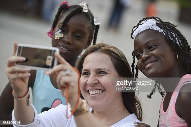 A woman takes a selfie with two AfroColombian girls during the 12th contest of Afro hairdressers Tejiendo Esperanzas in Cali Valle del Cauca...