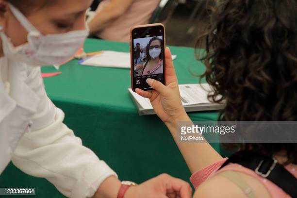 Woman takes a self-portrait inside a vaccination unit at Campo Marte, Mexico City, after being inoculated with a dose of the Pfizer-BioNTech biologic...