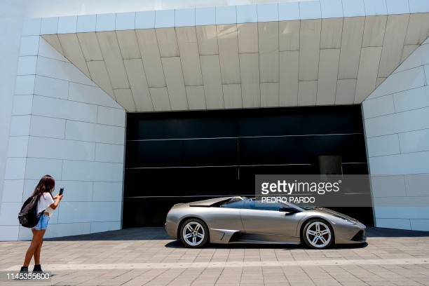 A woman takes a snapshot of a seized Lamborghini that will be auctioned taken at Los Pinos former presidential residence in Mexico City on May 21...
