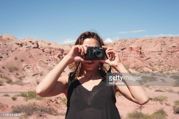 a woman takes a snapshot on a road trip through argentina - heshphoto - fotografias e filmes do acervo