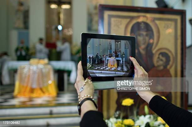 A woman takes a snapshot with her iPad of the altar with the relics of blessed John Paul II at the Medalha Milagrosa sanctuary in Rio de Janeiro...