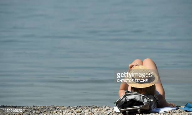A woman takes a sun bath at the banks of lake Ammersee in Utting southern Germany where temperatures were expected to reach up to 35 degrees Celsius...