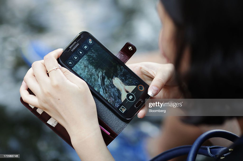 A woman takes a video of her feet with a Samsung Electronics Co. smartphone at Cheonggye Stream in Seoul, South Korea, on Wednesday, July 3, 2013. Samsung Electronics lost $25.3 billion in market capitalization last month, more than the value of competitor Sony Corp., as sales of its flagship Galaxy S4 smartphone fell short of investor expectations. Photographer: Woohae Cho/Bloomberg via Getty Images