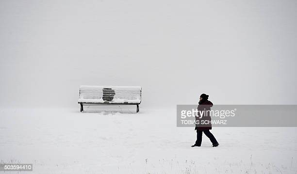 TOPSHOT A woman takes a walk at river Spree on a cold winter day in Berlin on January 6 2016 / AFP / TOBIAS SCHWARZ