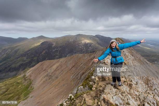 Woman takes careful steps on mountain ridge.