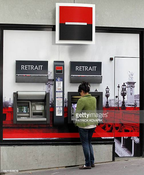 A woman takes cash at an ATM of French bank Societe Generale on September 12 2011 in Paris The French stock market plunged by 427 percent in early...