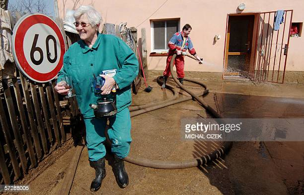 Woman takes coffee to her neighbour while her son hoses the backyard 08 April 2006 after the recent floods that hit the Czech Republic last week, in...