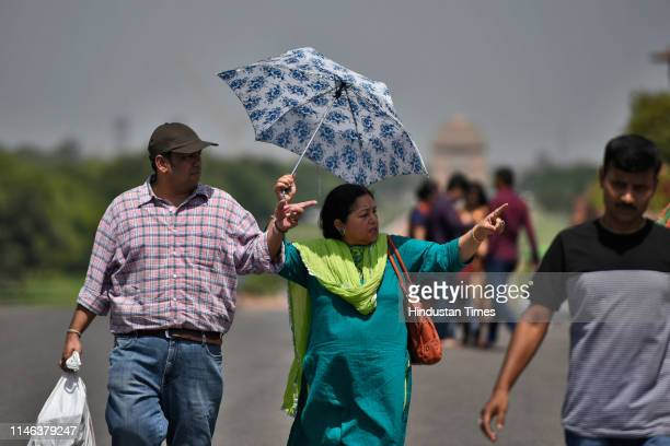 A woman takes cover under an umbrella to protect herself from the scorching sun on a hot day at Raisina Hills on May 26 2019 in New Delhi India...