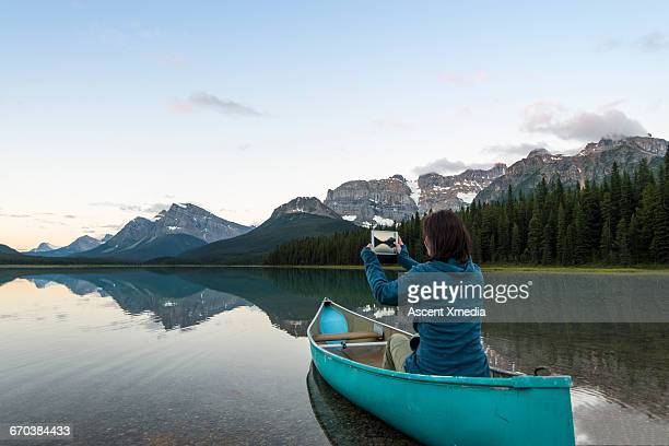 Woman takes digital tablet pic from canoe,mtn lake