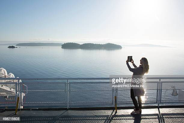 woman takes digital tablet picture on board ferry - passenger craft stock pictures, royalty-free photos & images