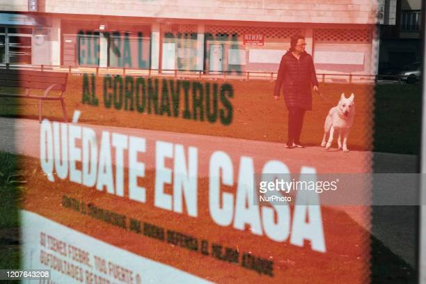 Woman takes her dog for a walk in a reflection in one of the street signs in which the population is asked to be quarantined in Gijon. Asturias,...