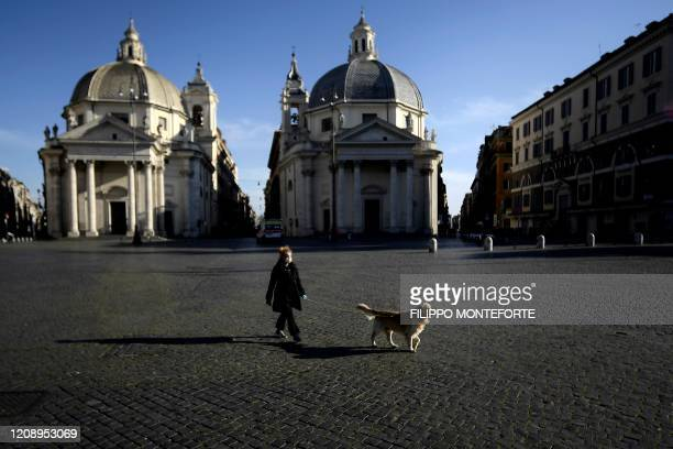A woman takes her dog out in Piazza del Popolo on April 2 2020 in Rome during the country's lockdown aimed at curbing the spread of the COVID19...