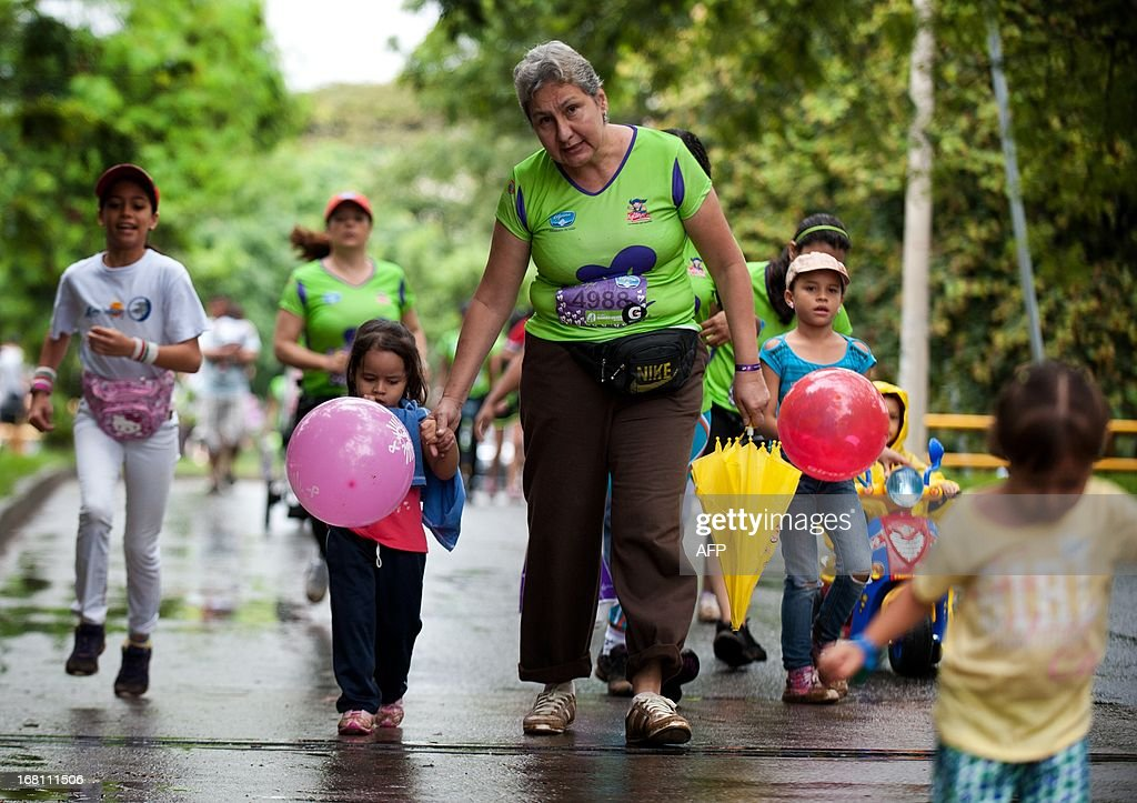 A woman takes her granddaughter by the hand during the 'Race of Women' in Cali, Colombia, on May 5, 2013. Thousands of women, some with their children, took part in the race held in support of the fight against breast cancer and violence against women. AFP PHOTO/Luis ROBAYO